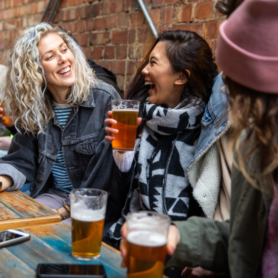 Women at bar drinking beer outdoors